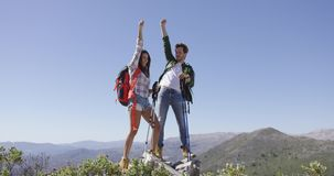Happy couple giving high five. Young delightful couple giving high five to each other while standing on plat of mountain in summer stock video