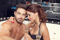 Happy couple with glasses of champagne in jacuzzi Royalty Free Stock Photo