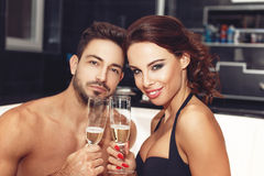 Happy couple with glasses of champagne in jacuzzi Stock Image