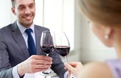 Happy couple with glasses of wine at restaurant Stock Images