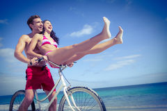 Happy couple going on a bike ride. At the beach Royalty Free Stock Images