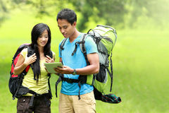 Happy couple going on a hike together looking at tablet pc in th Stock Photos