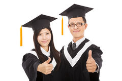 Happy couple graduate students with thumbs up Royalty Free Stock Image