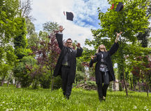 Happy Couple in the Graduation Day. Running in a park and throwing  their hats up Royalty Free Stock Images