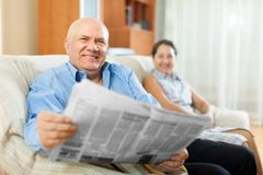 Happy couple of grandparents with newspaper royalty free stock photo