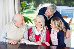 Happy Couple With Grandparents Reading Book In Stock Photo