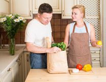 Happy couple with grocery paper bag with vegetables in kitchen. stock photo