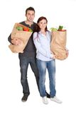 Happy couple with grocery shopping bags Royalty Free Stock Images