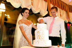 Happy couple groom and beautiful bride cutting delicious wedding Royalty Free Stock Photo