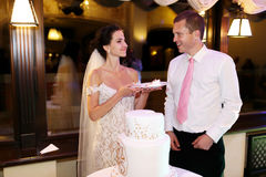 Happy couple groom and beautiful bride cutting delicious wedding Royalty Free Stock Photos