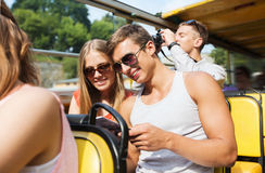 Happy couple with guidebook traveling by tour bus Royalty Free Stock Photo