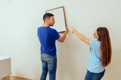 A young married couple decorates their new home royalty free stock photography