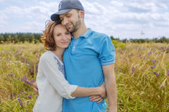 The happy couple has a rest in the field Royalty Free Stock Image