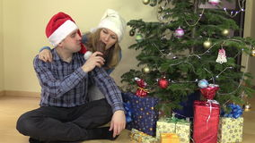 Happy couple with hat eat delicious Santa shape chocolate. Happy couple man and woman eat with hats eat delicious Santa shape chocolate. Decorated Christmas tree stock footage