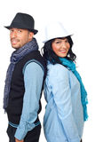 Happy couple with hats back to back Royalty Free Stock Image