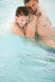Happy couple have fun under water stream in pool Stock Photo