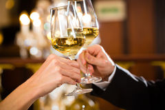 Happy couple have a romantic date in restaurant. Happy couple have a romantic date in a fine dining restaurant they drink wine and clinking glasses, cheers Royalty Free Stock Image