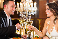 Happy couple have a romantic date in restaurant. Happy couple have a romantic date in a fine dining restaurant they drink wine and clinking glasses, cheers - a Royalty Free Stock Image
