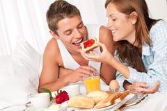 Happy couple having breakfast. Happy couple having luxury hotel breakfast in bed together Stock Images