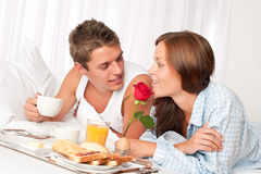 Happy couple having breakfast. Happy couple having luxury hotel breakfast in bed together Stock Photo