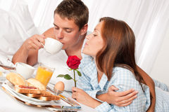 Happy couple having breakfast. Happy couple having luxury hotel breakfast in bed together Royalty Free Stock Image