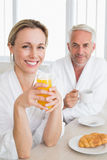 Happy couple having breakfast in bathrobes Royalty Free Stock Photos