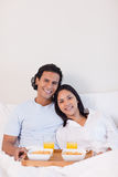 Happy couple having breakfast in the bed Royalty Free Stock Images