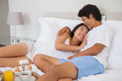 Happy couple having breakfast in bed Stock Photo