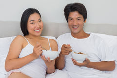Happy couple having breakfast in bed Royalty Free Stock Photo