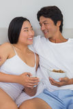 Happy couple having breakfast in bed Royalty Free Stock Photos