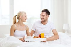 Happy couple having breakfast in bed at home. People, love, care and happiness concept - happy couple having breakfast in bed at home Royalty Free Stock Image
