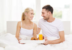 Happy couple having breakfast in bed at home Stock Photos