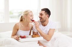 Happy couple having breakfast in bed at home. People, love, care and happiness concept - happy couple having breakfast in bed and eating strawberries at home Royalty Free Stock Photography