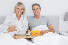 Happy couple having breakfast in bed. And smiling at the camera Stock Photography