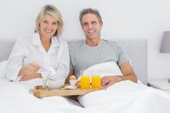 Happy couple having breakfast in bed Stock Photography