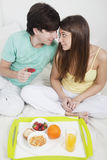 Happy couple having breakfast in bed Stock Images