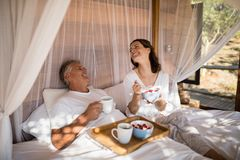 Happy couple having breakfast in canopy bed Stock Photos
