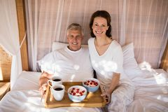 Happy couple having breakfast in canopy bed royalty free stock image