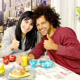 Happy couple having breakfast in front of skyscrapers in city looking camera thumb up Royalty Free Stock Images