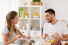 Happy couple having breakfast at home. Eating and people concept - happy couple having breakfast at home Royalty Free Stock Photography