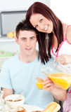 Happy couple having breakfast in the kitchen Royalty Free Stock Photography