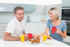 Happy couple having breakfast in kitchen Stock Photo