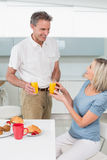 Happy couple having breakfast in kitchen Stock Images