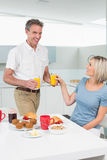 Happy couple having breakfast in kitchen Royalty Free Stock Images