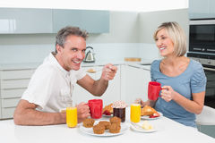 Happy couple having breakfast in kitchen Royalty Free Stock Photos