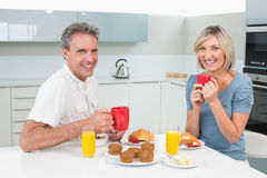 Happy couple having breakfast in kitchen Stock Photography