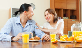 Happy couple having breakfast with scrambled eggs and oranges Royalty Free Stock Photos