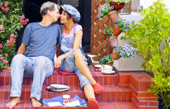 Happy couple having breakfast on the terrace. Middle-age happy couple having breakfast on the terrace, face to face, tenderly and caress Royalty Free Stock Image