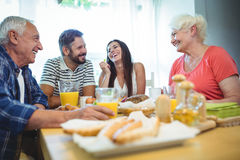 Happy couple having breakfast with their parents stock image