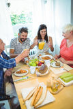 Happy couple having breakfast with their parents stock photography